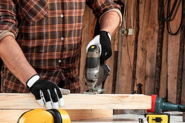 Um carpinteiro de homem corta uma viga de madeira usando um quebra-cabeça elétrico, mãos masculinas com um close de quebra-cabeça elétrico.