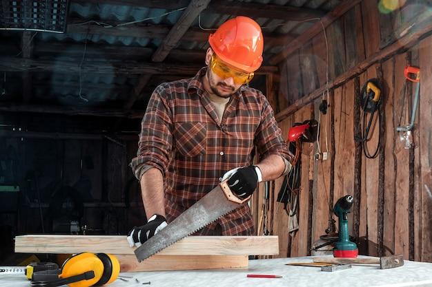 Um carpinteiro de homem corta uma viga de madeira usando uma serra manual, mãos masculinas com uma serra closeup.