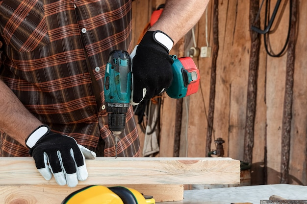 Um carpinteiro de homem torce um parafuso em uma árvore com uma chave de fenda elétrica, mãos masculinas com um close de chave de fenda.