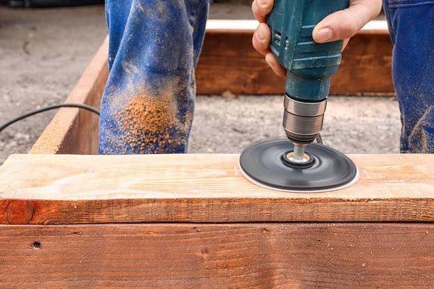 Um carpinteiro de macacão azul processa um produto de madeira usando uma ferramenta profissional