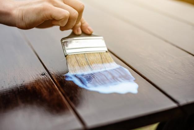 Um carpinteiro de madeira aplica uma camada protetora de verniz transparente
