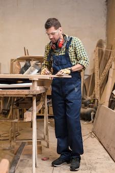 Um carpinteiro masculino ativo, medindo a prancha de madeira na oficina