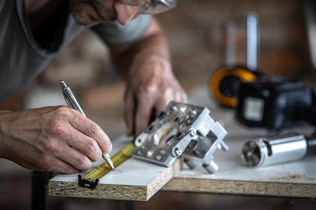 Um carpinteiro no processo, uma ferramenta profissional para perfurações de precisão em madeira.