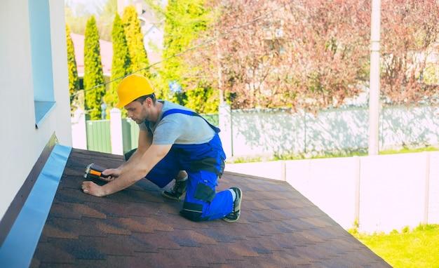 Um carpinteiro profissional de uniforme e capacete de segurança com um martelo na mão está consertando o telhado da nova casa