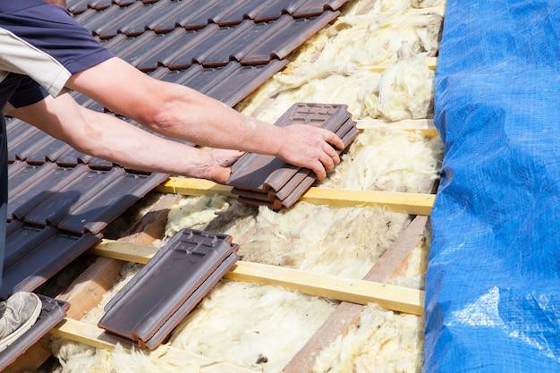 Um carpinteiro que coloca a telha no telhado