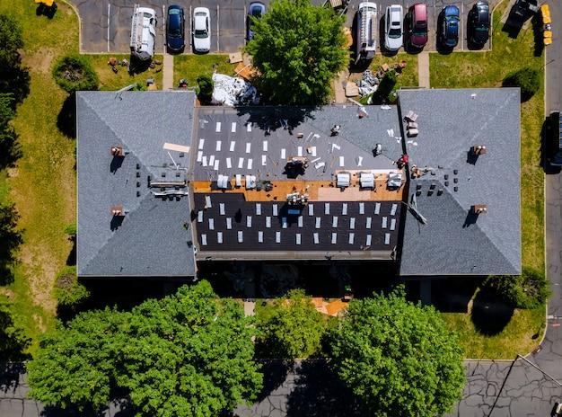 Um carpinteiro que prega as telhas com pistola de ar, substituindo a proteção da cobertura do telhado sendo aplicada