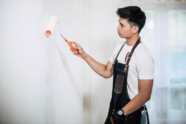 Um carpinteiro segura um pincel e pinta madeira.