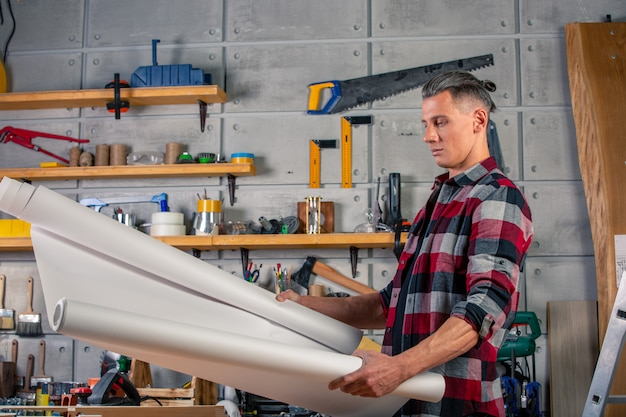 Um carpinteiro trabalha. carpinteiro, estudando o projeto de desenho. no contexto do workshop