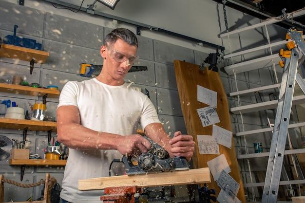 Um carpinteiro trabalha com madeira na máquina-ferramenta. serrar detalhes de móveis com serra circular