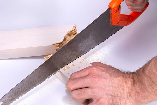 Um carpinteiro trabalha em uma serra manual para cortar uma tábua de madeira quebrada