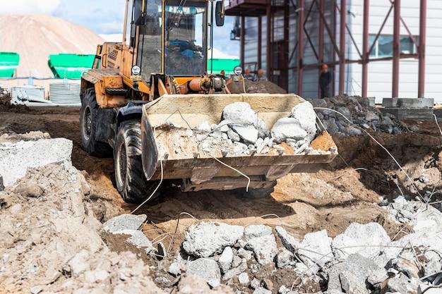 Um carregador frontal em um canteiro de obras remove detritos do concreto armado. recolha e retirada de materiais de construção separados.