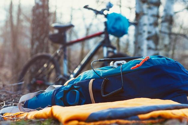 Um carregador portátil carrega o smartphone. banco de potência com cabo no contexto de madeira e bicicleta.