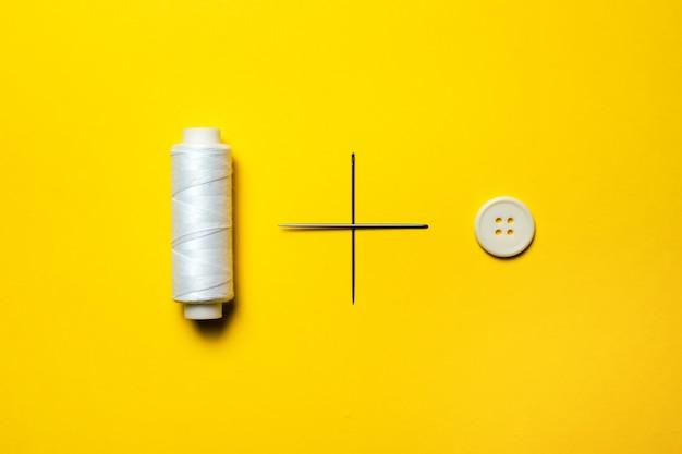 Um carretel de linha branca, agulhas de bordado que formam um sinal de mais e um botão branco estão enfileirados