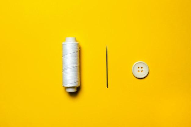 Um carretel de linha branca, uma agulha de bordado e um botão branco estão enfileirados