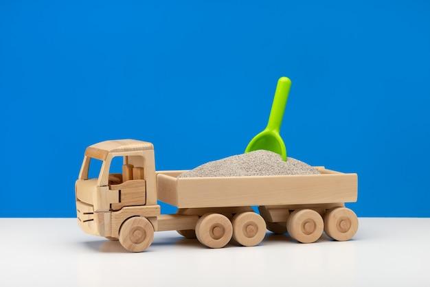 Um carrinho de brinquedo de madeira em miniatura cheio de areia com uma pá verde. diversão para meninos, close-up azul