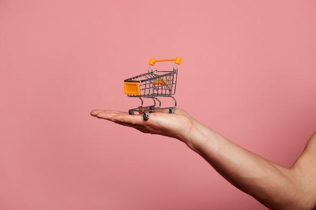 Um carrinho de compras. carrinho de compras de brinquedo, que está parado na mão de um homem.