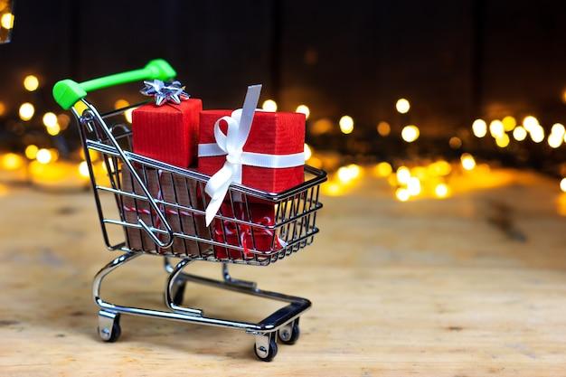 Um carrinho de compras cheio de presentes de natal contra um fundo de luzes desfocadas.