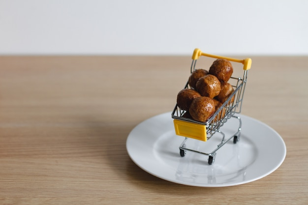 Um carrinho de compras do supermercado está cheio de almôndegas. o conceito de comprar comida