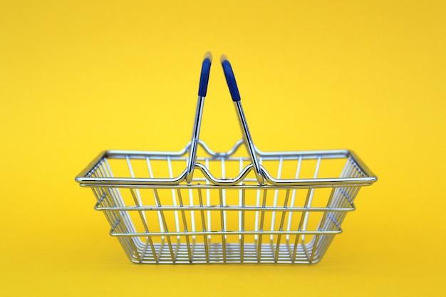 Um carrinho de compras em miniatura de ferro vazio fica em uma parede amarela. tema de negócios, compras e comida.