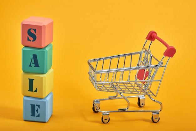 Um carrinho de compras em miniatura e cubos multicoloridos em um fundo amarelo