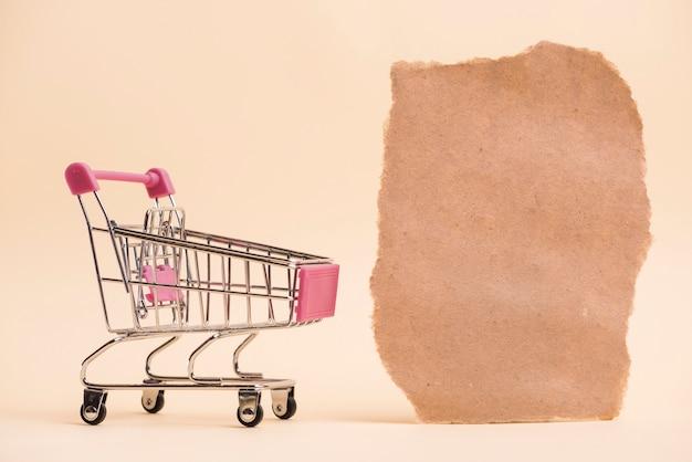 Um carrinho de compras em miniatura vazio perto do pedaço de papel rasgado contra o pano de fundo colorido