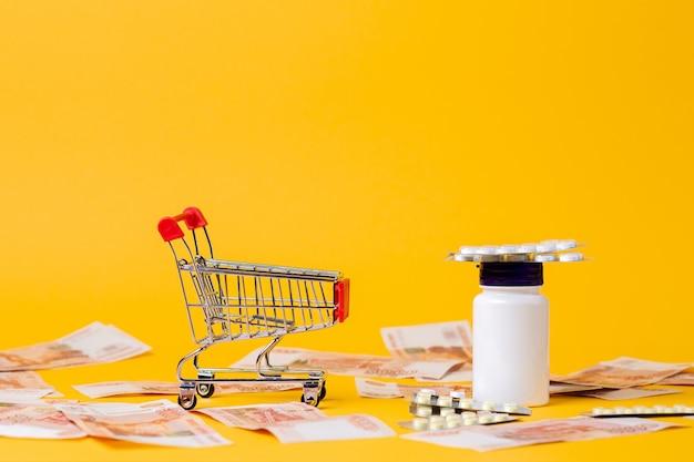 Um carrinho de compras vazio e um frasco de comprimidos. fundo amarelo com dinheiro espalhado. copie o espaço. o conceito de alto custo dos medicamentos