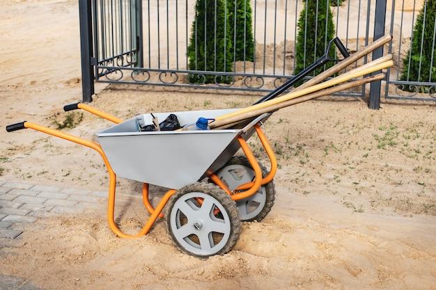 Um carrinho de mão cheio de ferramentas e equipamentos de construção. preparação para o trabalho. movimentação de cargas no canteiro de obras.