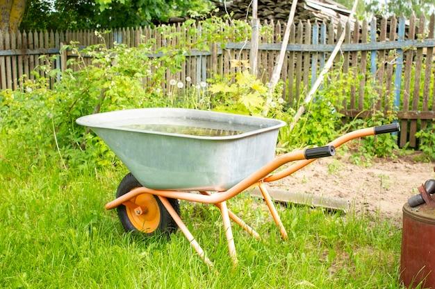 Um carrinho de mão de jardim fica no quintal de uma fazenda nas proximidades de ferramentas adicionais