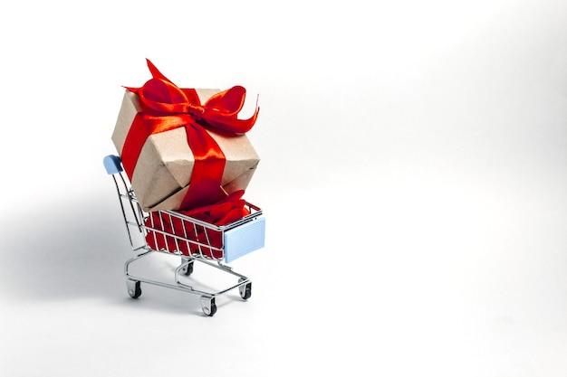 Um carrinho de supermercado cheio até a borda com corações de confete vermelhos e uma caixa de presente embrulhada em papel kraft e amarrada com uma fita vermelha