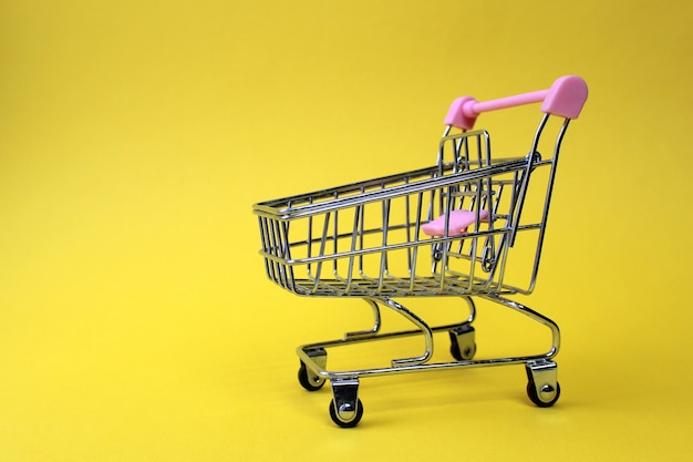 Um carrinho de supermercado de ferro em miniatura vazio fica em uma parede amarela brilhante com espaço para texto. tema comercial e de negócios.