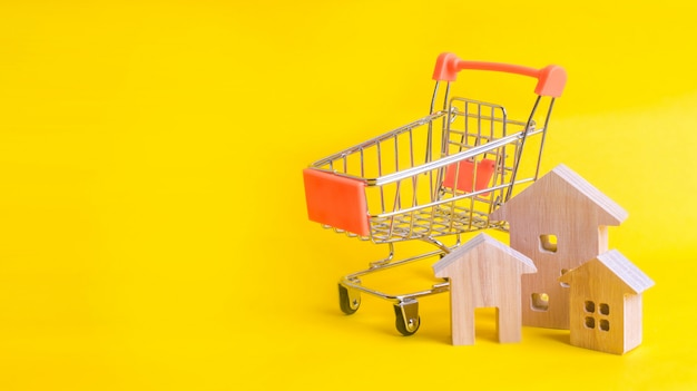 Um carrinho de supermercado e casas em um fundo amarelo.