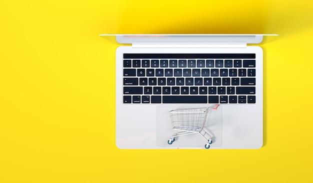 Um carrinho em cima de um computador laptop para o conceito de compras on-line, negócios de comércio eletrônico e fundo de marketing