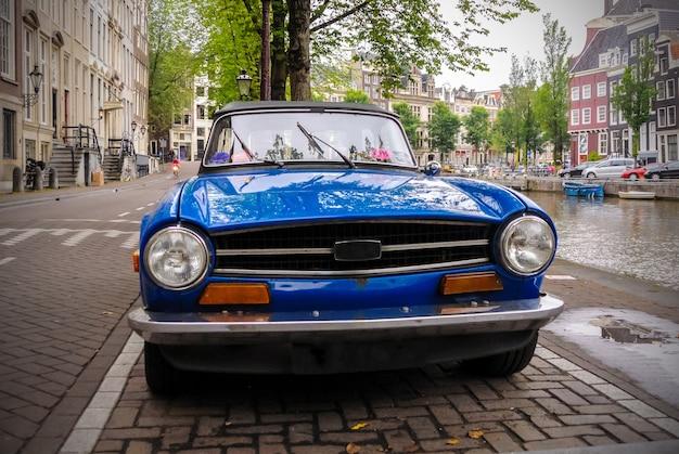 Um carro azul antigo está estacionado na rua ao longo de um canal em amsterdã, holanda