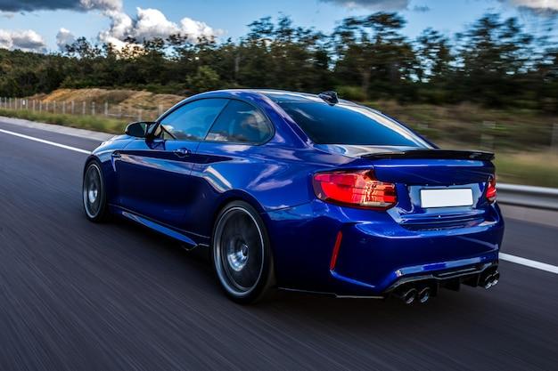 Um carro azul dirigindo na estrada.