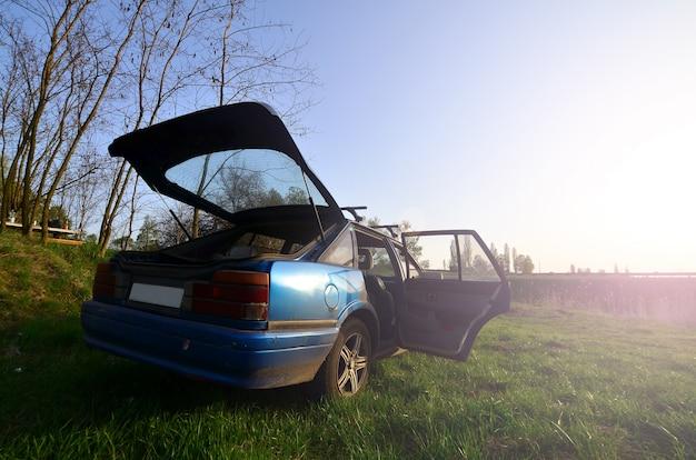 Um carro azul em um fundo de uma paisagem rústica com um campo selvagem do bastão e um lago pequeno. a família veio descansar na natureza perto do lago