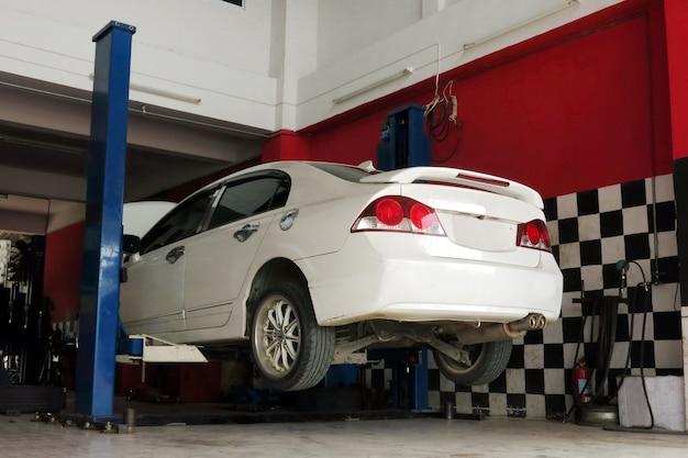 Um carro branco é levantado para o processo de reparação