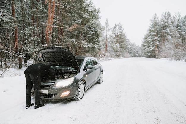 Um carro com capô aberto no fundo de uma floresta de inverno