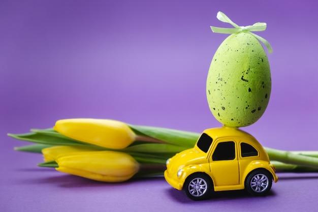 Um carro de brinquedo amarelo carrega um ovo verde em uma superfície roxa