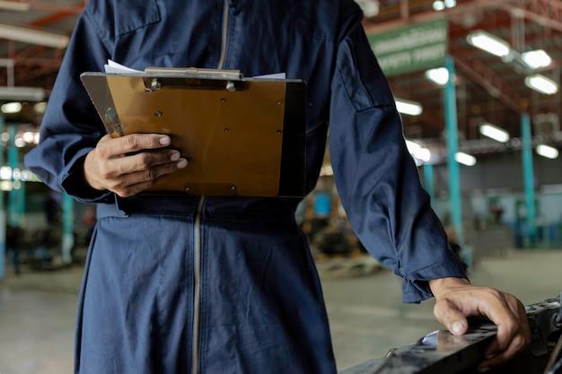 Um carro de serviço mecânico na garagem é verificar uma lista de carros.