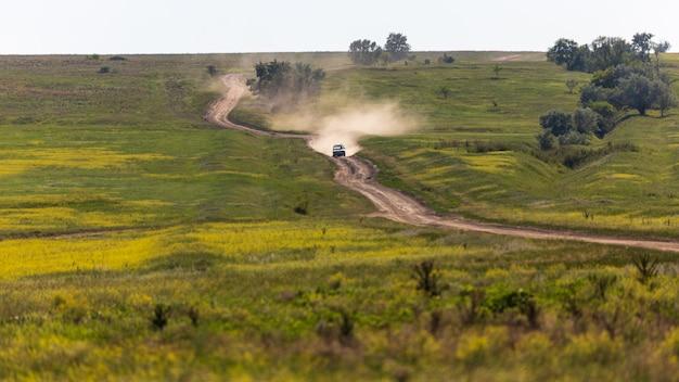 Um carro dirige ao longo de uma encosta, ao longo de uma estrada rural, deixando para trás uma nuvem de poeira