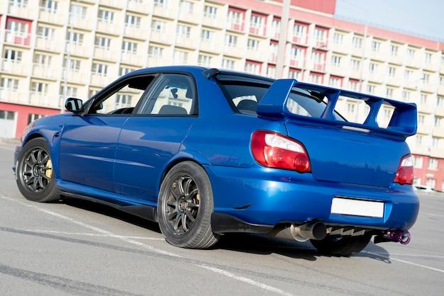 Um carro esporte azul moderno de corrida rápida na pista no dia de treino de verão