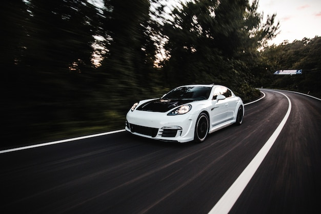 Um carro esporte branco com ajuste automático preto dirigindo com alta velocidade na estrada.