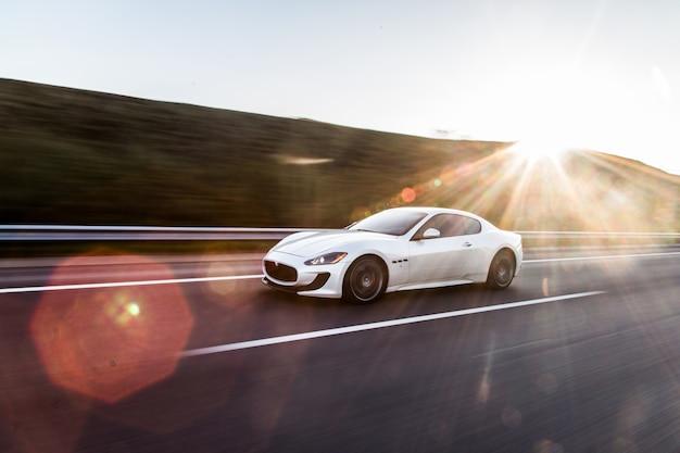 Um carro esporte branco dirigindo na estrada.