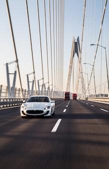 Um carro esporte branco sedan dirigindo na ponte.