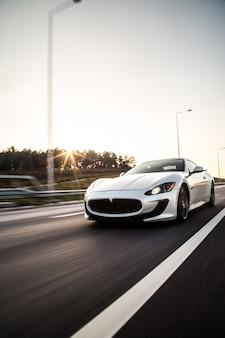 Um carro esporte de cor metálica tira com alta velocidade na estrada.