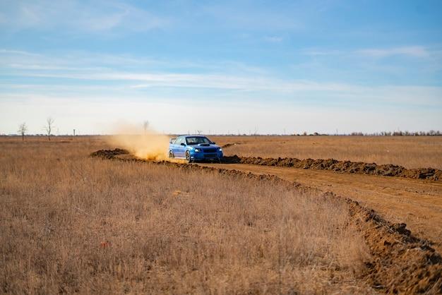 Um carro esporte de rally dirigindo na corrida de cascalho drit, velocidade rápida com respingos de lama