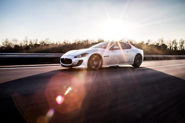 Um carro esporte prateado de alta velocidade, dirigindo na estrada no tempo ensolarado.