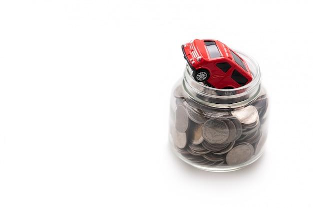 Um carro modelo vermelho em muitas moedas em uma jarra de vidro isolado no fundo branco e cópia espaço, poupança e conceito de investimento