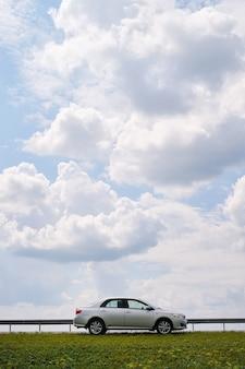 Um carro prateado está estacionado ao lado de uma estrada deserta em uma área rural, contra um céu azul com nuvens e um campo verde.