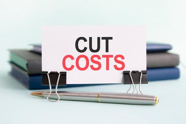 Um cartão branco com o texto cortando custos fica em um clipe para papéis sobre a mesa contra o fundo de livros. foco seletivo